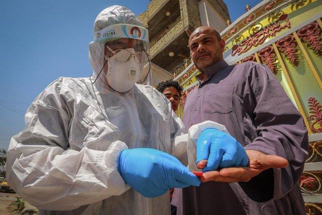 Un trabajador sanitario de Irak toma una muestra de sangre durante la pandemia de coronavirus