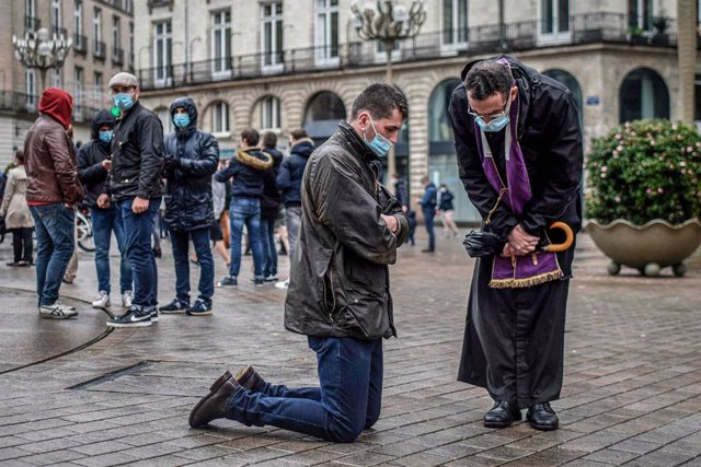 FILED - 15 November 2020, France, Nantes: A Catholic priest listens to the confession of a believer during a gathering to call the reopening of places of worship as the national lockdown in France counties to stop the spread of the coronavirus. Photo: Seb