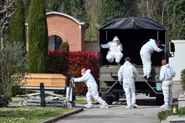 dpatop - 21 March 2020, Italy, Ferrara: People in protective suits transport a coffin with a corpse of the deceased due to the coronavirus in the cemetery of Ferrara. Military vans are having to transport coffins from Bergamo to other Italian cities, as t