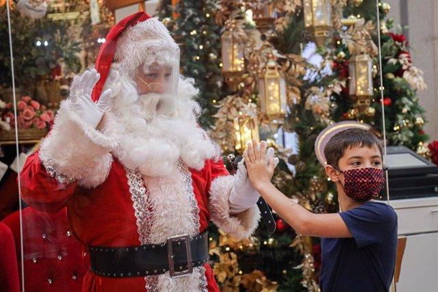 Un niño con mascarilla saluda a un Santa Claus con pantalla protectora en Kuala Lumpur