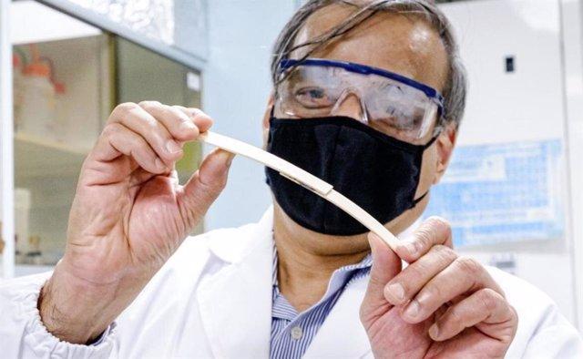 Un investigador de la NTU sujetando y doblando dos piezas de madera unidas en el medio por el pegamento de endurecimiento magnético, para demostrar su fuerte fuerza de unión.