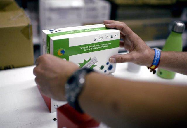 Una farmacéutica coloca una de las cajas de un test de antígeno para Covid-19, en Madrid (España). Como avanzó hace dos días la presidenta de la Comunidad de Madrid, Isabel Díaz Ayuso, se está estudiando que en las farmacias de la región se puedan hacer t