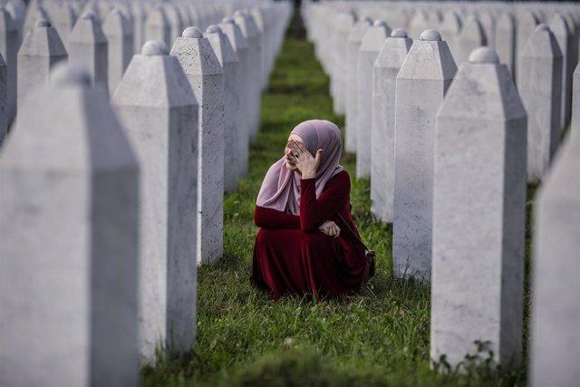 Una mujer llora ante la lápida de su familiar en el cementerio de Potocari, donde descansan los restos mortales de miles de víctimas del genocidio de Srebrenica