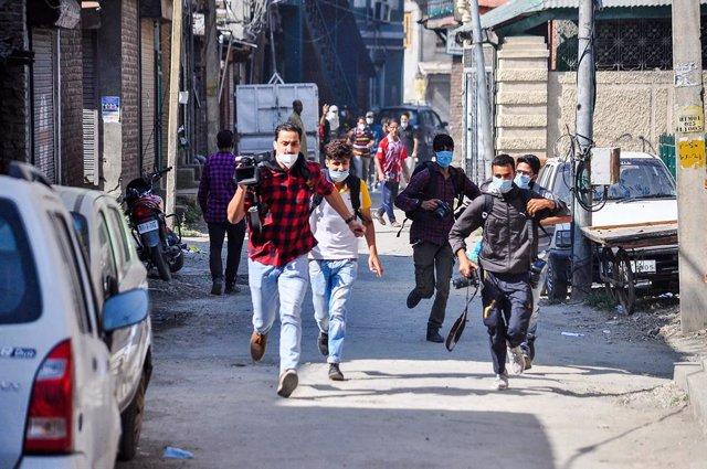 Un grupo de periodistas corre durante los enfrentamientos que tuvieron lugar en unas recientes manifestaciones en Cachemira por la muerte de tres personasa a manos de las autoridades de India.