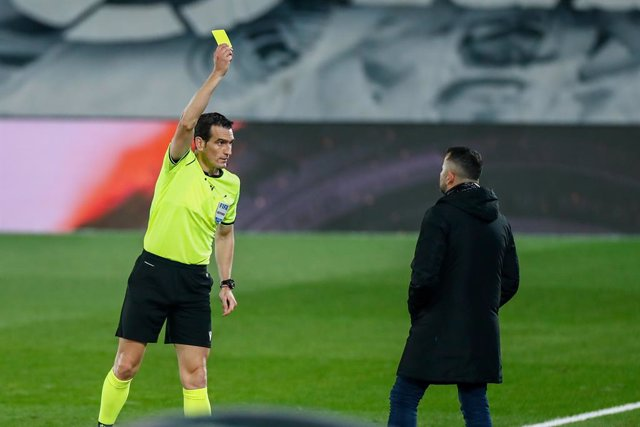Juan Martinez Munuera, referee of the match, shows the yellow card to Diego Martinez, head coach of Granada, during the spanish league, La Liga Santander, football match played between Real Madrid and Granada CF at Ciudad Deportiva Real Madrid on december