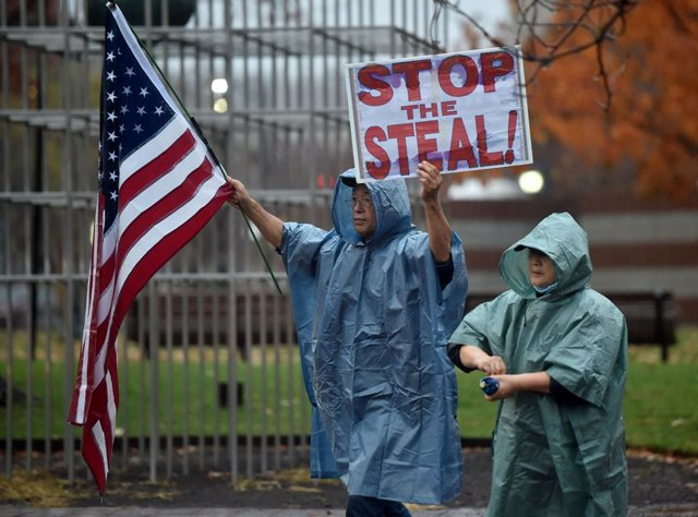 11 November 2020, US, Wilkes-Barre: A protester holds a placard and a US flag during a 'Stop the Steal' protest demanding a recount of votes in Pennsylvania. Photo: Aimee Dilger/SOPA Images via ZUMA Wire/dpa