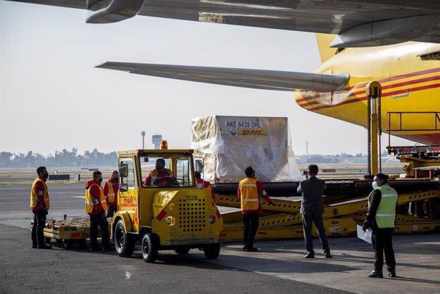 Trabajadores del aeropuerto de Ciudad de México descargan cargamento de la vacuna de Pfizer.