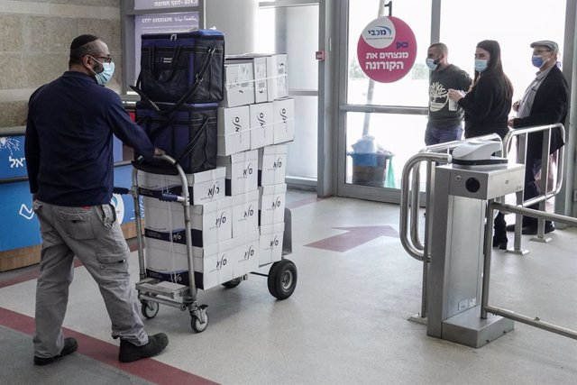 21 December 2020, Israel, Jerusalem: A person delivers boxes of Pfizer-Biontech's Corona vaccine to the Pais Arena sports complex, where the Maccabi Health Organization is preparing to administer the vaccine to public. Photo: Nir Alon/ZUMA Wire/dpa