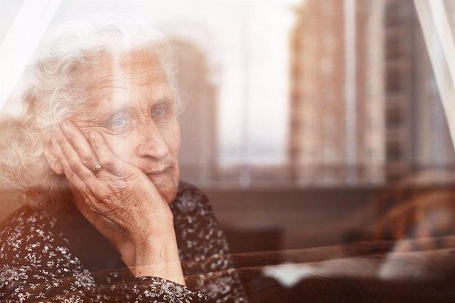 Mujer mayor sentada sola y triste tras una ventana.