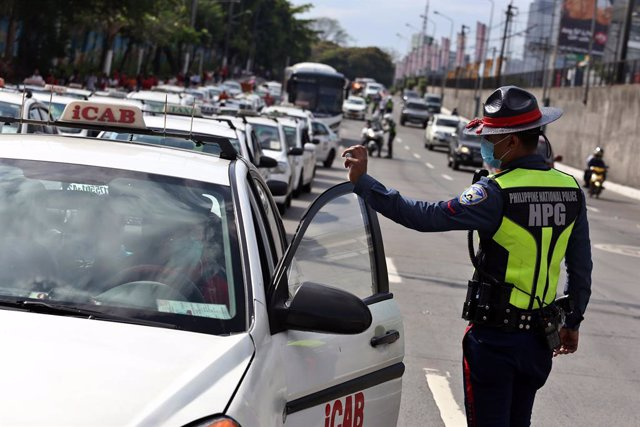 """17 March 2020, Philippines, Manila: A policeman talks to a driver near a checkpoint in Manila. President Duterte has placed the whole of Luzon - the largest island in the Philippines with 57 million people - under """"tightened quarantine"""" and tightened the"""