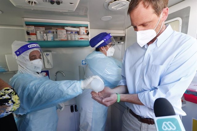 09 October 2020, Chile, Vina Del Mar: A health care worker helps officer Arturo Zuniga (R) disinfect his hands at a Covid-19 testing station. Photo: Leonardo Rubilar/Agencia Uno/dpa
