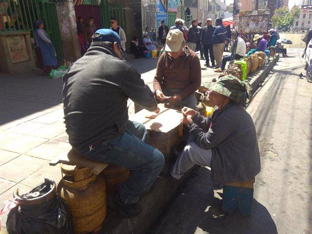 Bolivianos esperan para hacerse con bombonas de gas en La Paz.