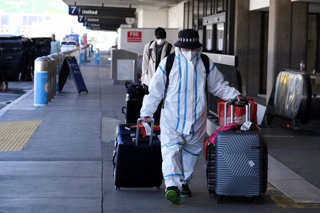 22 December 2020, US, Los Angeles: A passenger wearing personal protective equipment arrives at the Los Angeles International Airport. Photo: Ringo Chiu/ZUMA Wire/dpa