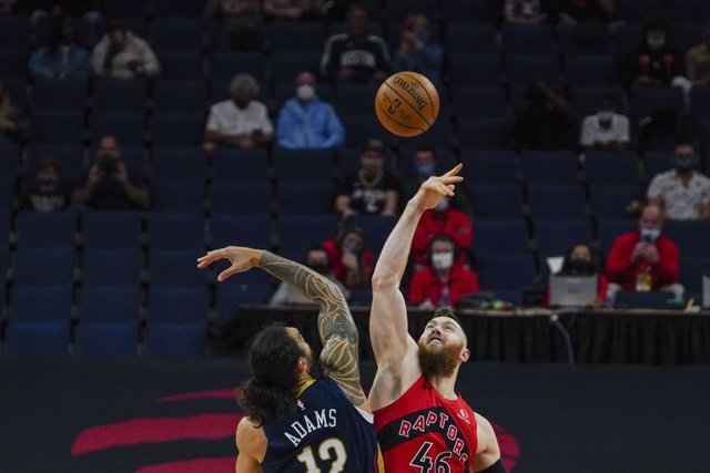 23 December 2020, US, Tampa: Toronto Raptors player Aron Baynes (R) and New Orleans Pelicans player Naji Marshall battle for the ball during the NBA basketball match between Toronto Raptors and New Orleans Pelicans at Amalie Arena. Photo: Martha Asencio R