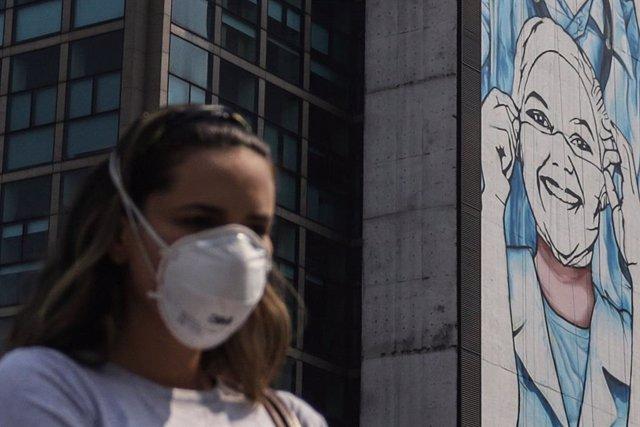 Una mujer camina por la calle de Sao Paulo.