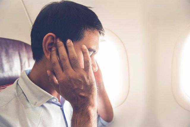 Hombre con oidos taponados en el avión.