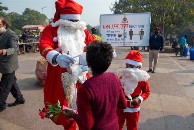Un hombre disfrazado de Papá Noel reparte mascarillas en Nueva Delhi
