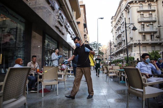 27 June 2016, Egypt, Cairo: A man sprays disinfectant outside a coffee following the easing of the Coronavirus (Covid-19) lockdown restrictions. Egyptian authorities allowed the partial reopening of businesses in an attempt to mitigate the economic impact