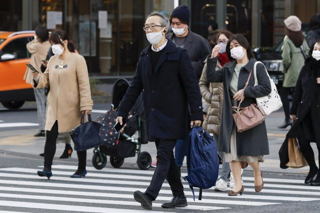 16 December 2020, Japan, Tokyo: People wearing face masks walk around the Ginza shopping district. Tokyo reached a new single-day record of 678 new coronavirus (COVID-19) cases on Wednesday. Photo: Rodrigo Reyes Marin/ZUMA Wire/dpa