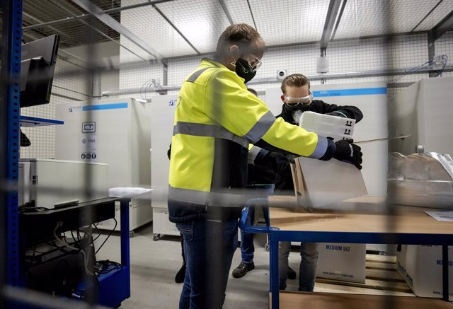 26 December 2020, Netherlands, Oss: Employees unpack the first doses of Pfizer/BioNTech coronavirus vaccines to be stored in a freezer of the company Movianto in the industrial park Vorstengrafdonk. The vaccines come from the Pfizer factory in Puurs, a to
