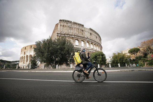 Un ciclista de reparto frente al Coliseo de Roma