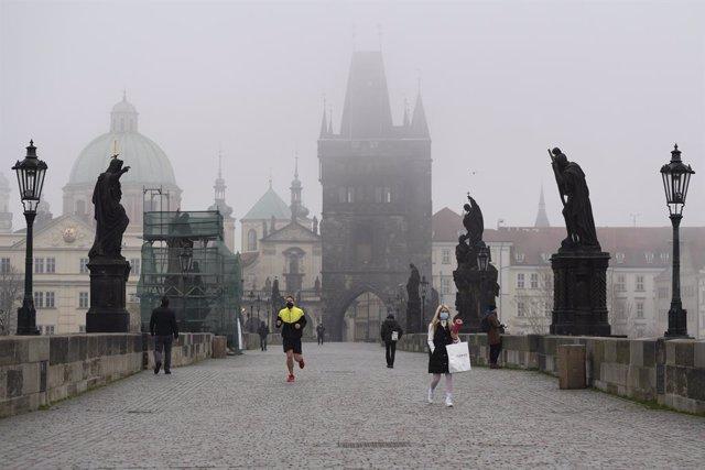 Personas con mascarilla recorriendo un puente de Praga