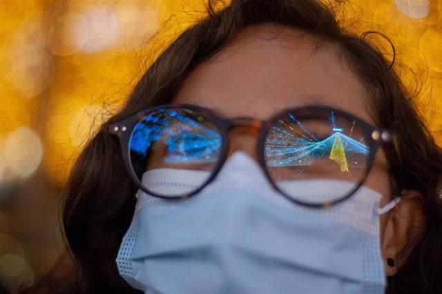 Una mujer en Colombia viendo las luces de Navidad con mascarilla en plena pandemia del coronavirus.
