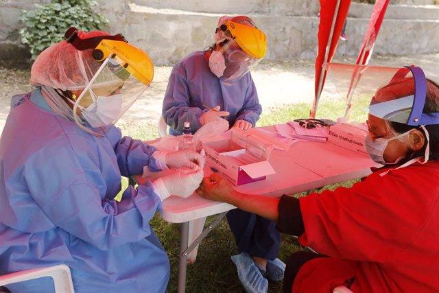 Una trabajadora sanitaria realiza pruebas rápidas del coronavirus en Perú.