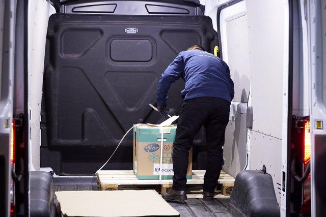Un operario entrega una caja con dosis de la vacuna de Pfizer y BioNTech en la residencia Los Olmos, el primer día de vacunación contra la Covid-19 en España, en la residencia de mayores Los Olmos de Guadalajara, en Castilla La-Mancha (España),