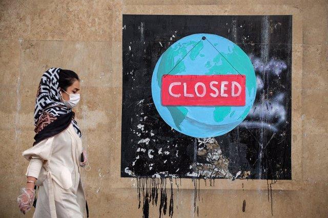 Una mujer ante un graffiti en la capital de Irán, Teherán, durante la pandemia de coronavirus