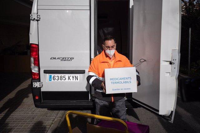 Un operari porta la caixa amb les dosis de la vacuna contra la Covid-19 la residència de majors Feixa Llarga de L'Hospitalet de Llobregat