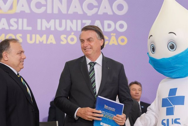 HANDOUT - 16 December 2020, Brazil, Brasilia: Brazilian President Jair Bolsonaro poses for a photo with the mascot Ze Gotinha, a traditional character in Brazil created to raise awareness about the coronavirus vaccines, during the launch of the National V