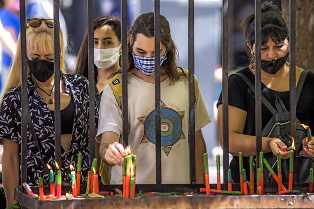 03 December 2020, Argentina, Buenos Aires: People wearing face masks light candles as they pray. Photo: Roberto Almeida Aveledo/ZUMA Wire/dpa