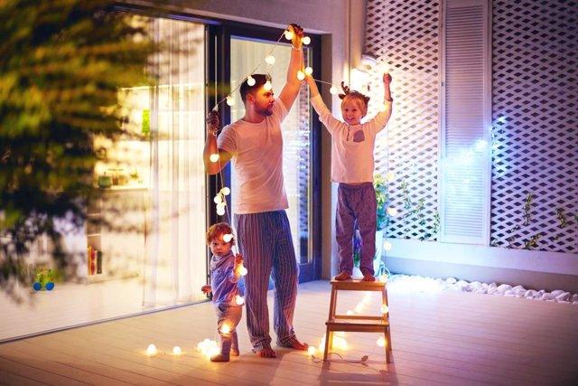 Padre con sus hijos colocando una guirnalda de luces navideñas-