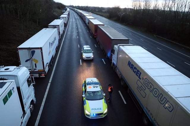 22 December 2020, England, Ashford: A lorry driver talks to police officers as they patrol along the M20 in Kent where lorries are parked after the Port of Dover was closed and access to the Eurotunnel terminal was suspended following the French governmen