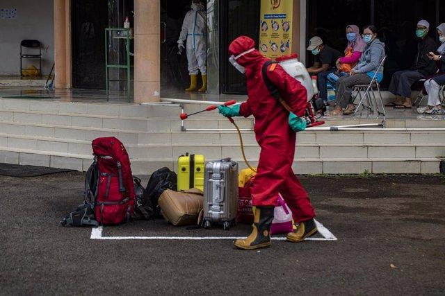 Desinfección del equipaje de varias personas en Indonesia durante la pandemia de coronavirus