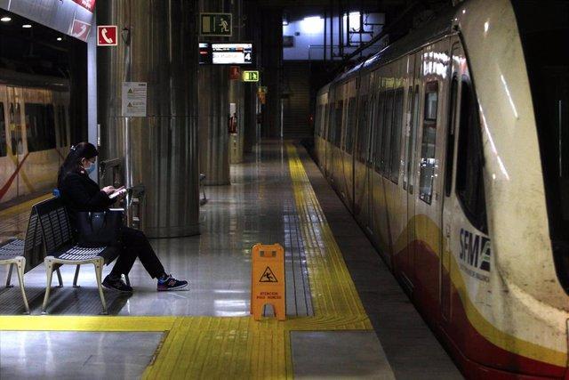 Una mujer protegida con mascarilla espera la llegada del metro en la estación Intermodal.