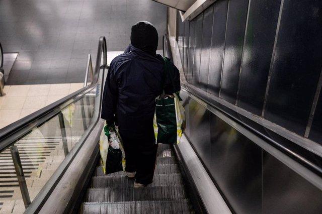 Un usuario baja las escaleras mecánicas de una de las estaciones de Metro de Madrid durante la tercera semana de confinamiento por coronavirus, en Madrid (España), a 31 de marzo de 2020.