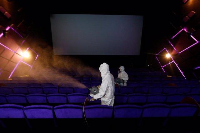 Trabajadores con trajes protectores desinfectando un cine en Bangkok