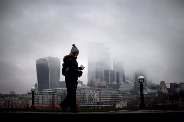 28 December 2020, England, London: A woman walk past a view of the City of London which is covered in low mist. Photo: Victoria Jones/PA Wire/dpa