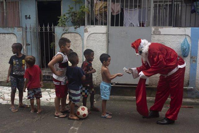23 December 2020, Brazil, Rio De Janeiro: A man dressed as Santa Claus disinfects children's hands as a precaution measure against the Coronavirus, while handing out candy in the Mare favela. Photo: Fabio Teixeira/ZUMA Wire/dpa