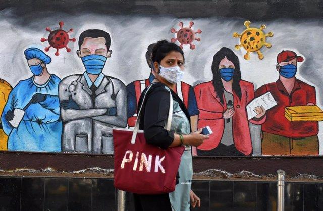 Una mujer con mascarilla pasa ante un mural con trabajadores con mascarilla en Bombay