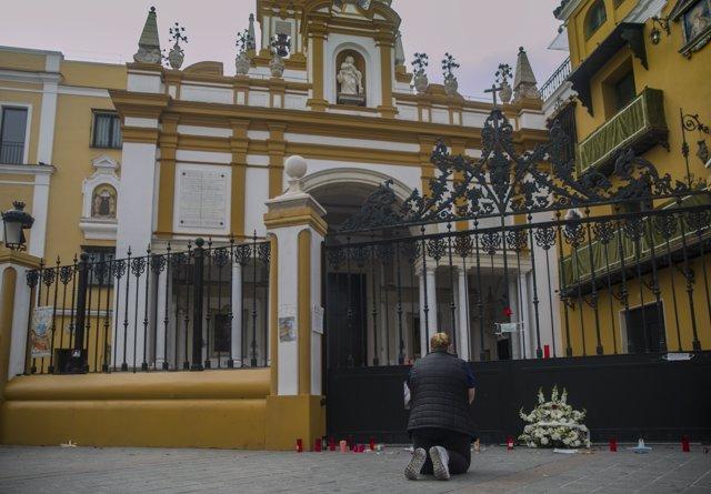 Una mujer se arrodilla ante la Basílica de la Macarena durante el estado de alarma. En Sevilla (Andalucía, España), a 10 de abril de 2020.