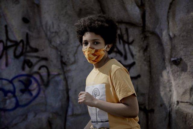 El niño actor y modelo Hugo Ndiaye, de 10 años, pasea el primer día en el que los menores de 14 años de la Comunidad de Madrid pueden realizar paseos entre las 10 y las 13 horas y entre las 17 y las 21 horas, tras decidir la Comunidad de Madrid flexibiliz
