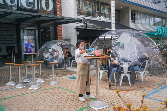 26 December 2020, Colombia, Bogota: A waitress serves food to customers who sit inside a capsule as a biosecurity measure due to the spread of coronavirus (COVID-19). Photo: Daniel Garzon Herazo/ZUMA Wire/dpa