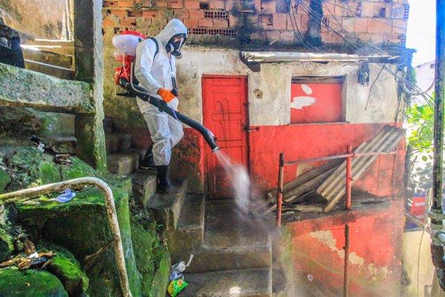 Una persona desinfecta una favela en Río de Janeiro.