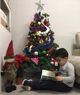 Fotografía de recurso de un niño leyendo un libro junto al árbol de Navidad