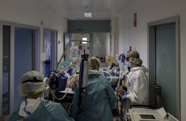 Personal sanitario totalmente protegido trasladan a un paciente ingresado en la del UCI del Infanta Sofía en San Sebastián de los Reyes