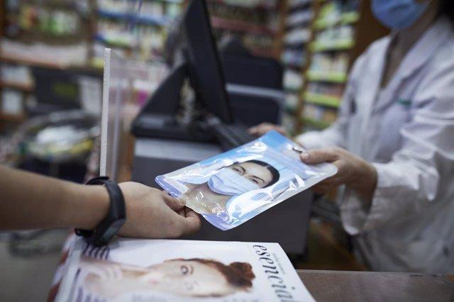 Una farmacéutica enseña a un cliente un paquete de mascarillas en la farmacia situada en la calle Tucán, 7, en el distrito de Carabanchel, Madrid (España), a 11 de noviembre de 2020.