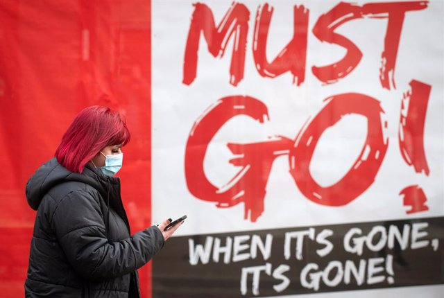 30 December 2020, England, Northampton: A woman wearing a face mask walks past a sign in a shop window, as further changes to England's tier system are expected to be announced, just days after millions of people came under harsher coronavirus restriction